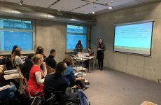 zdjęcie z konferencji, przedstawia ujęcie z boku sali na osoby słuchające wystąpienia siedzące w trzech pierwszych rzędach oraz prelegentkę na tle ekranu z prezentacją. Na tle okna widoczny stolik i dwie osoby, kierujące obradami