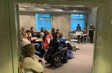 zdjęcie z konferencji, przedstawia ujęcie z boku sali na osoby słuchające wystąpienia siedzące w czterech pierwszych rzędach oraz prelegentkę, na tle okna widoczny stolik i dwie osoby, kierujące obradami