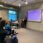 zdjęcie z konferencji, przedstawia ujęcie z boku sali na osoby słuchające wystąpienia siedzące w pierwszym rzędzie oraz prelegentki na tle ekranu z prezentacją, na tle okna widoczny stolik i dwie osoby, kierujące obradami
