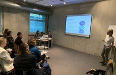 zdjęcie z konferencji, przedstawia ujęcie z boku sali na osoby słuchające wystąpienia siedzące w pierwszych dwóch rzędach oraz prelegentkę na tle flipchartu oraz ekranu z prezentacją. Na tle okna widoczny stolik i dwie osoby, kierujące obradami