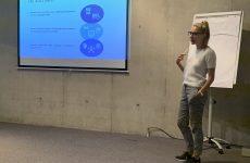 zdjęcie z konferencji, przedstawia ujęcie z boku sali na prelegentkę na tle flipchartu oraz ekranu z prezentacją