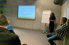 zdjęcie z konferencji, przedstawia ujęcie z boku sali na osoby słuchające wystąpienia siedzące w pierwszym rzędzie oraz prelegentkę na tle flipchartu oraz ekranu z prezentacją. Na tle okna widoczny stolik i dwie osoby, kierujące obradami