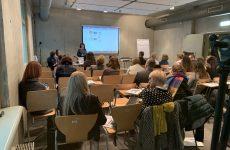 zdjęcie z konferencji, przedstawia ujęcie z tyłu sali na osoby słuchające wystąpienia oraz prelegentkę na tle ekranu z prezentacją. Z lewej strony przy stoliku widać też dwie osoby, kierujące obradami