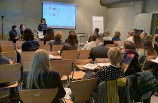 zdjęcie z konferencji, przedstawia ujęcie z tyłu sali na osoby słuchające wystąpienia oraz prelegentkę na tle ekranu z prezentacją. Z lewej strony przy stoliku widać też dwie osoby, kierujące obradami.