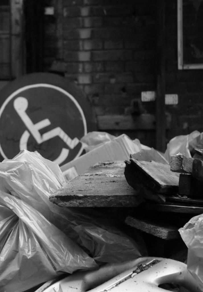 Na zdjęciu znak przedstawiający symbol osoby na wózku położony na stercie śmieci.