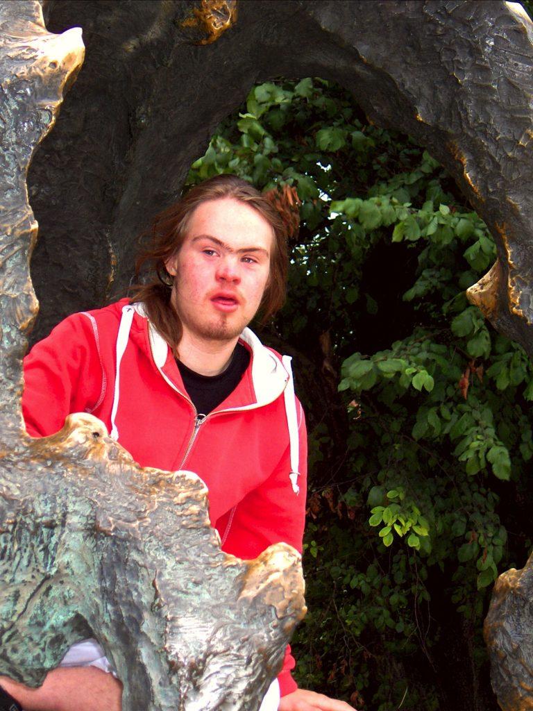 Na zdjęciu widzimy młodego mężczyznę z zespołem Downa, ubranego w czerwoną bluzę z kapturem i czarny podkoszulek, który jest widoczny gdyż górna część bluzy jest rozsunięta. Młody mężczyzna stoi pomiędzy nogami rzeźby smoka wawelskiego, w tle widzimy liście drzewa.