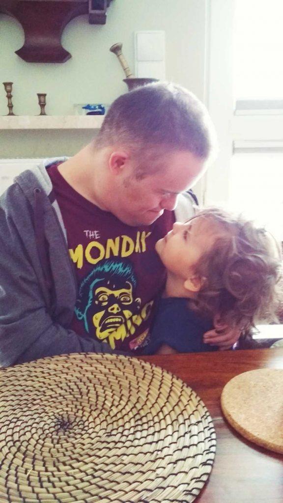 Na zdjęciu młody mężczyzna z zespołem Downa siedzi przy stole i przytula małą dziewczynkę, do której się nachyla